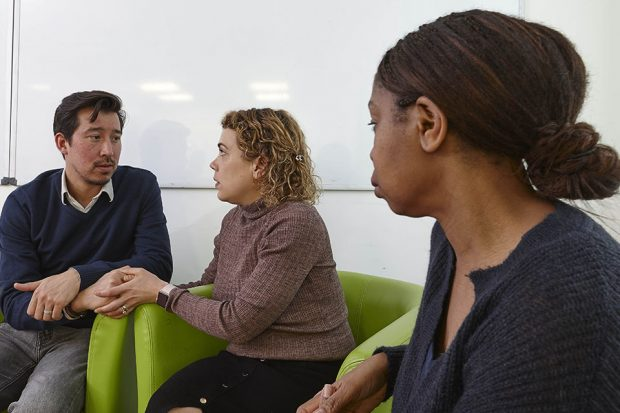 Counsellor looking at couple who are looking at each other seriously and holding hands